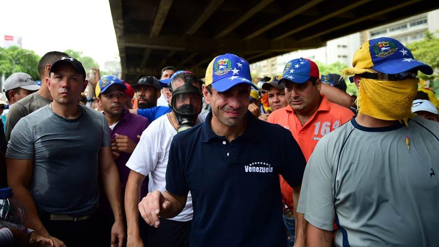 El líder de la oposición Henrique Capriles mientras sufre los efectos del gas lacrimógeno durante una manifestación contra el presidente venezolano Nicolás Maduro, en las calles de Caracas. Foto AFP/ Ronaldo Schemidt