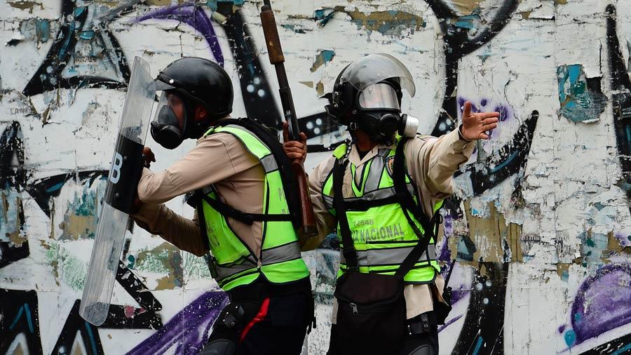 Policías antidisturbios se enfrentan a manifestantes durante una protesta contra el presidente venezolano Nicolás Maduro. Foto/ AFP