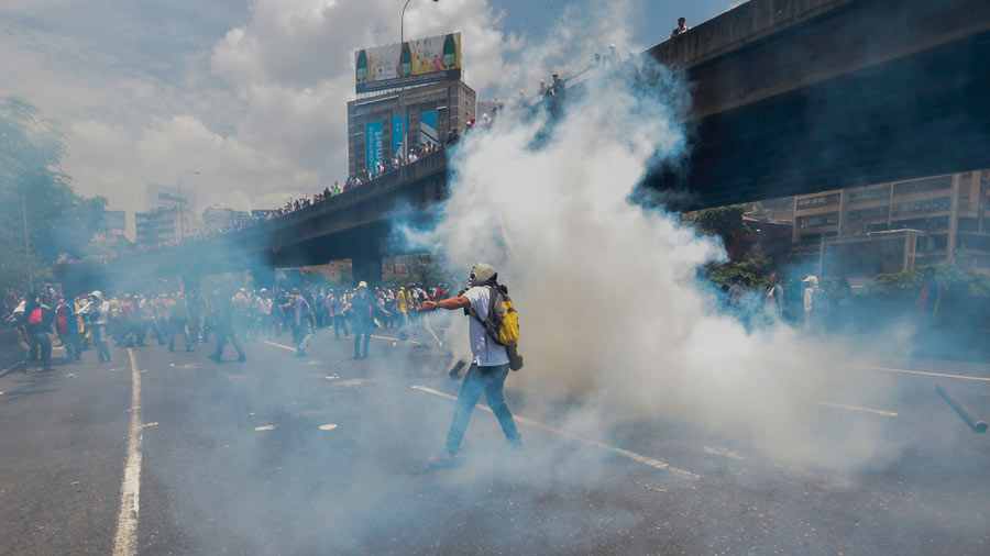 A demonstrator throws a tear gas canister back at the police during a