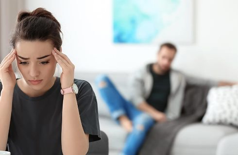 Young couple ignoring each other after having argument in living room